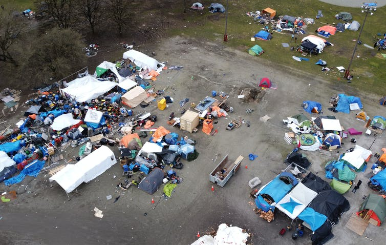Aerial photograph of a car park with tents and personal belongings