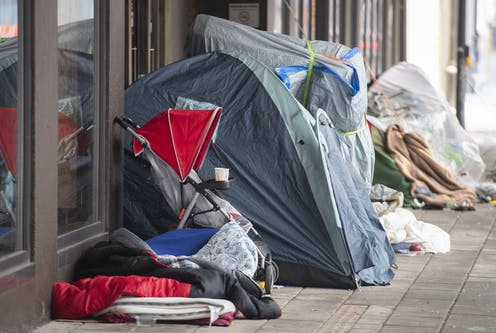 Homeless tents and a stroller next to department store doors