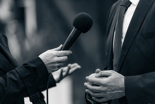 A microphone is held for an interview
