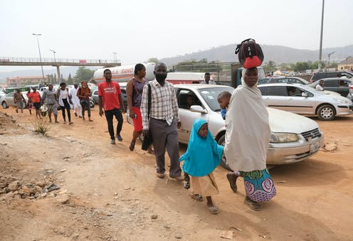 A woman holding a child and carefully balancing a baby on her back and a load on her head, leads a group of people walking on the road side in Abuja, Nigeria's capital city.