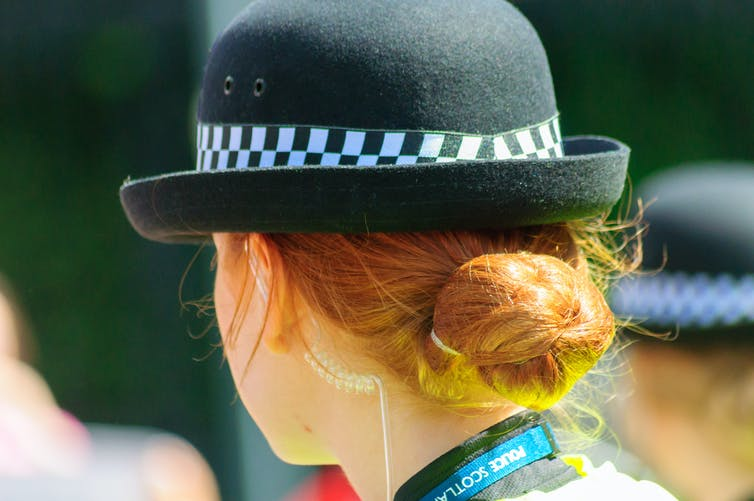 Closeup of the back of the head of a female police officer.