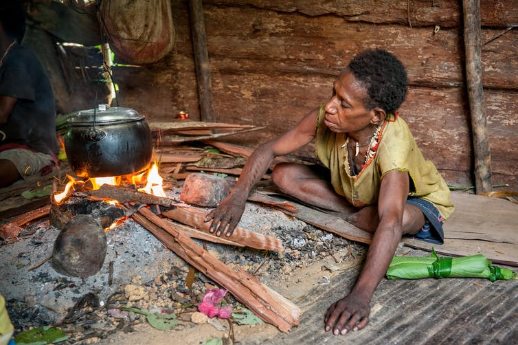 A PNG resident cooks over a fire