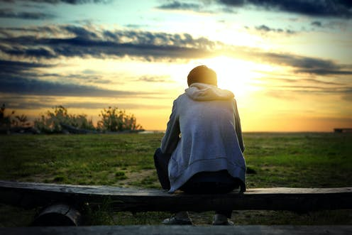 Young man sitting on fence and watching sunset.