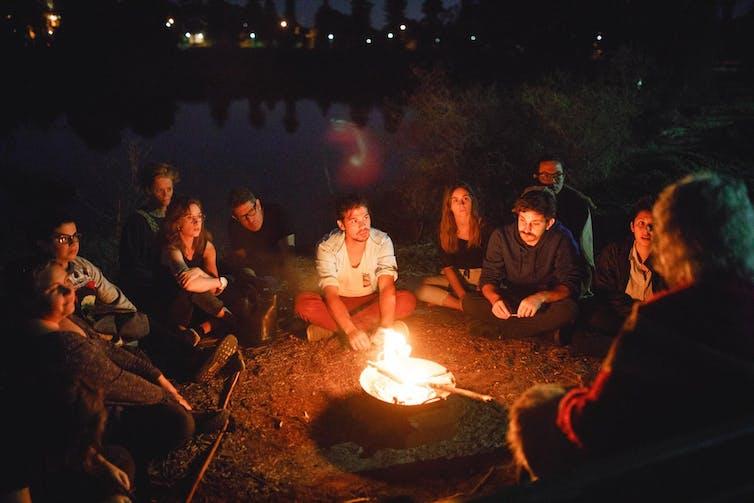 people sitting around campfire