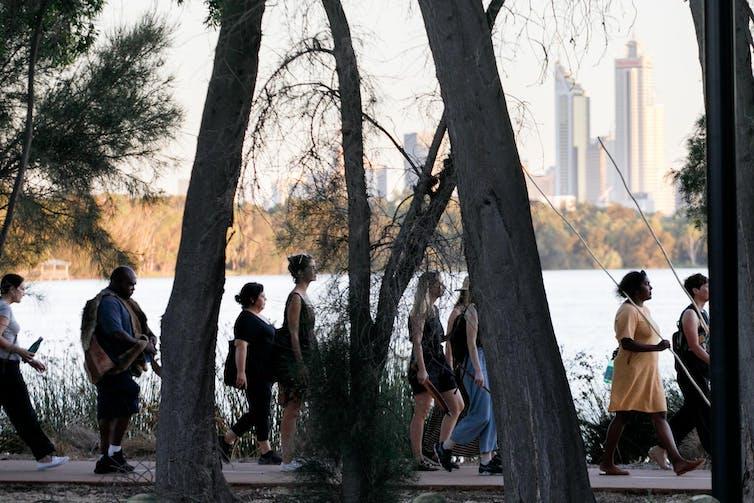 People walk alongside lake, city buildings