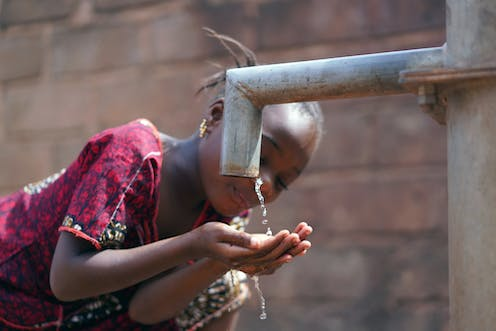 A young girl drinking water from an outdoor pump.
