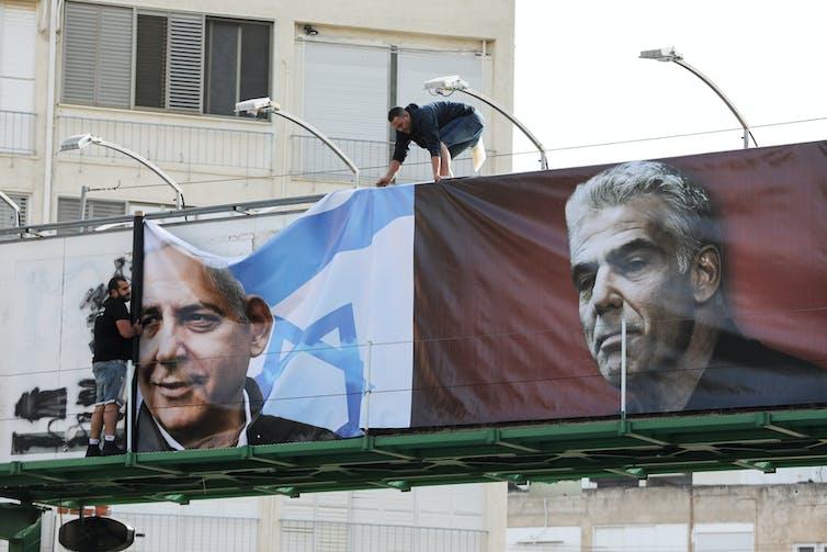 Men hang a large banner showing prime minister Benjamin Netanyahu and opposition leader Yair Lapid.