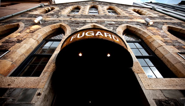 An entrance to a venue, a metal sign reading 'Fugard', the camera pointing up from street level revealing a church-like old stone structure a few storeys high.