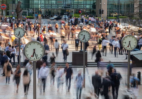 Blurred people walking through Canary Wharf with clocks in the foreground
