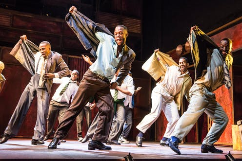 On stage, half a dozen men dance, one arm pulling up their jackets in unison, smartly dressed in 1950s city attire, smiling as they move.
