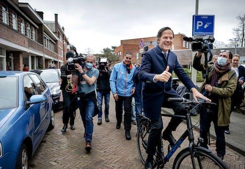 Dutch prime minister cycling down a street as press photographers follow him.