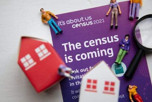 Figurines of house and people on top of census 2021 information booklet