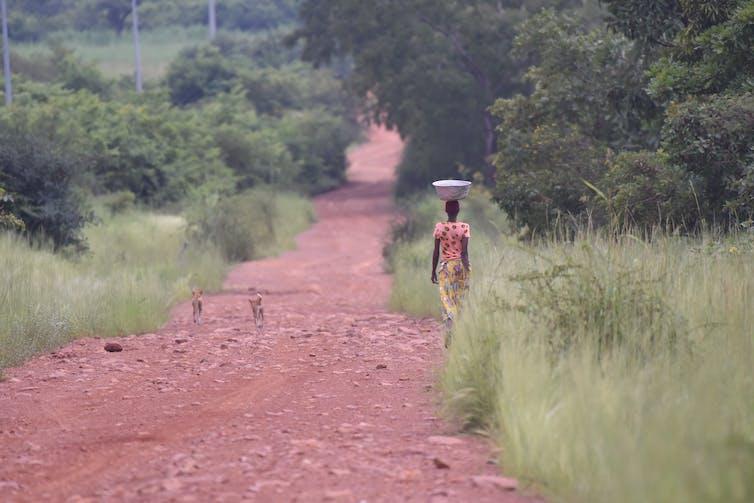 A woman walks along a road by Pendjari National Park