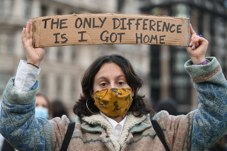 A woman holding a sign reading 'The only difference is, I got home.'