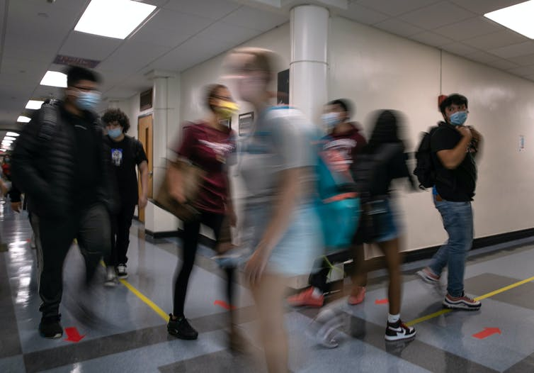 High school students pass each other in hallway