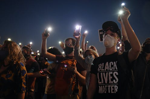 Demonstrators hold up cell phones during a protest