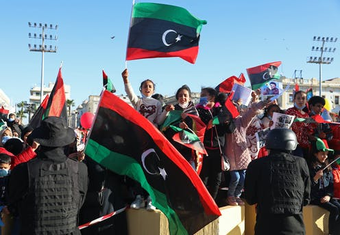 Libyans wave flags in a public square.