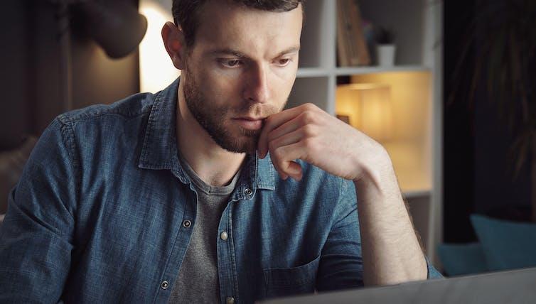 Young man looking at computer screen.