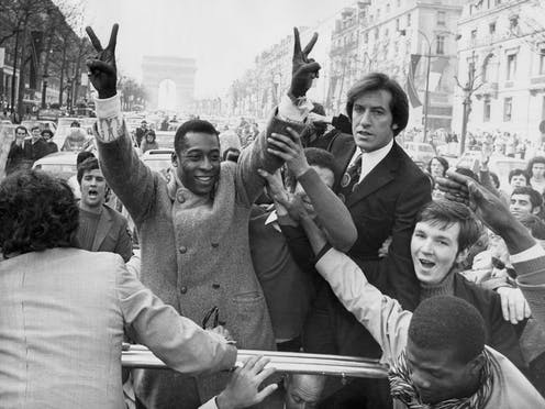 Pele flashes victory signs.