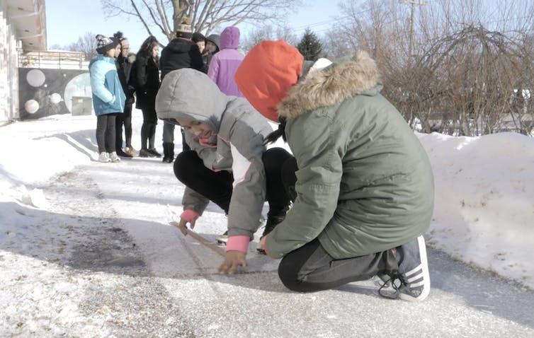 Kids work together on sidewalk in snow