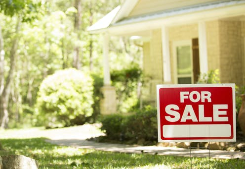 'For Sale' sign in yard of a house