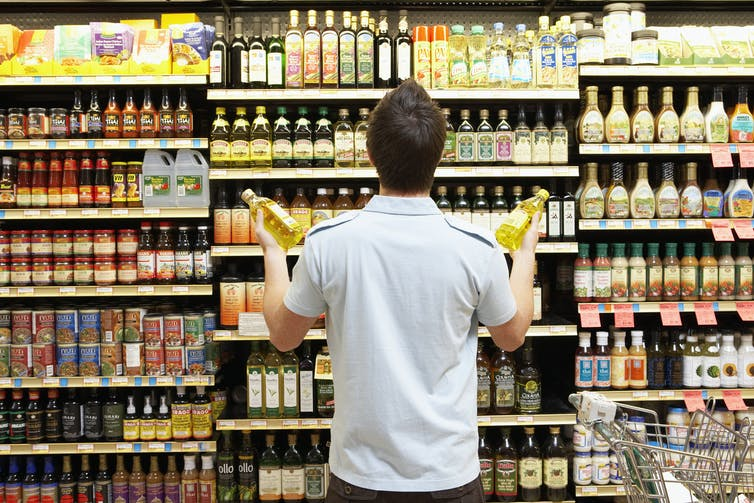 man looking at full grocery shelves