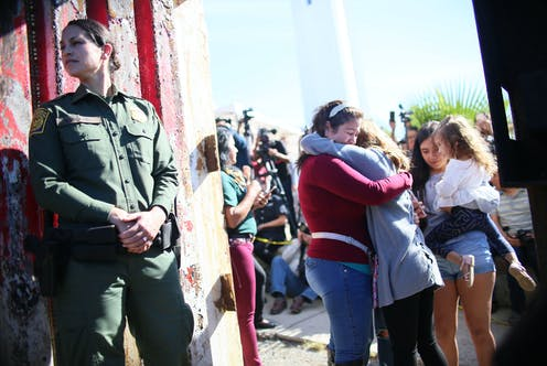 Border patrol guard looks over her shoulder next to border fence as women hug in the background