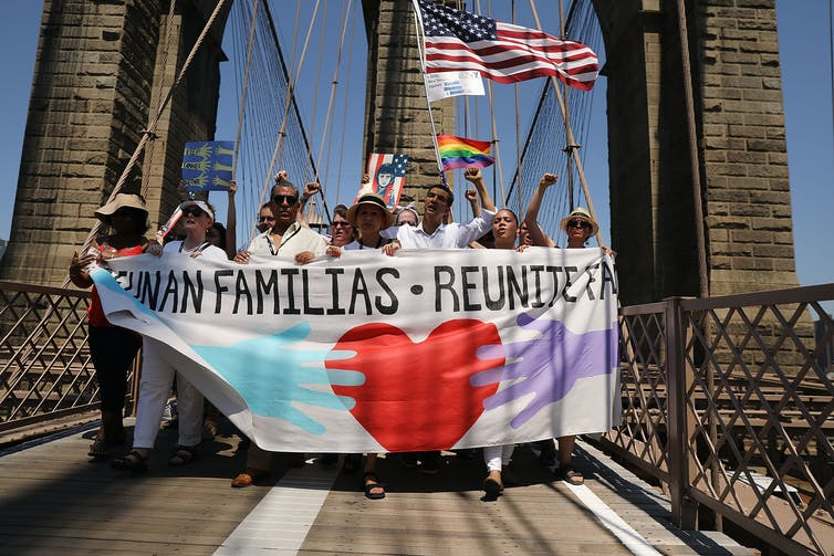 Group crosses the Brooklyn Bridge holding signs that promote 'Reunited Families' and an American flag