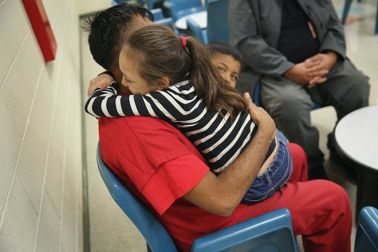 Small girl in striped shirt hugs a man in a red jumpsuit, in an institutional setting