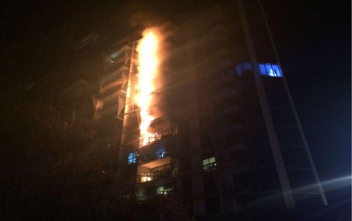 flames going up the side of an apartment building through the cladding
