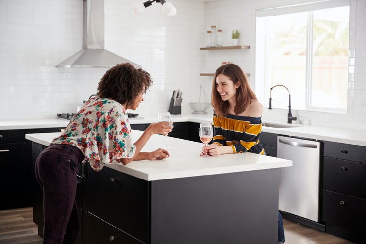 Two women drinking wine at a kitchen island bench.