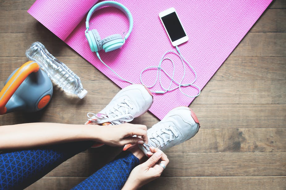 Woman lacing up her running shoes next to her headphones, smartphone, water bottle, kettlebell, and yoga mat.