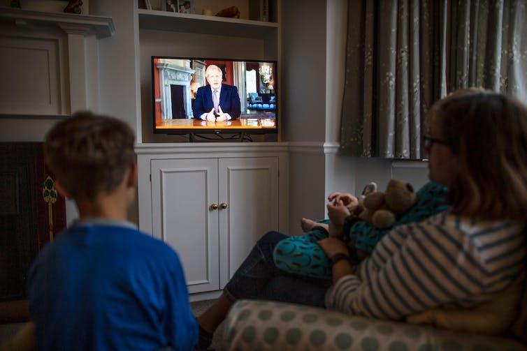 A family watches Boris Johnson on TV