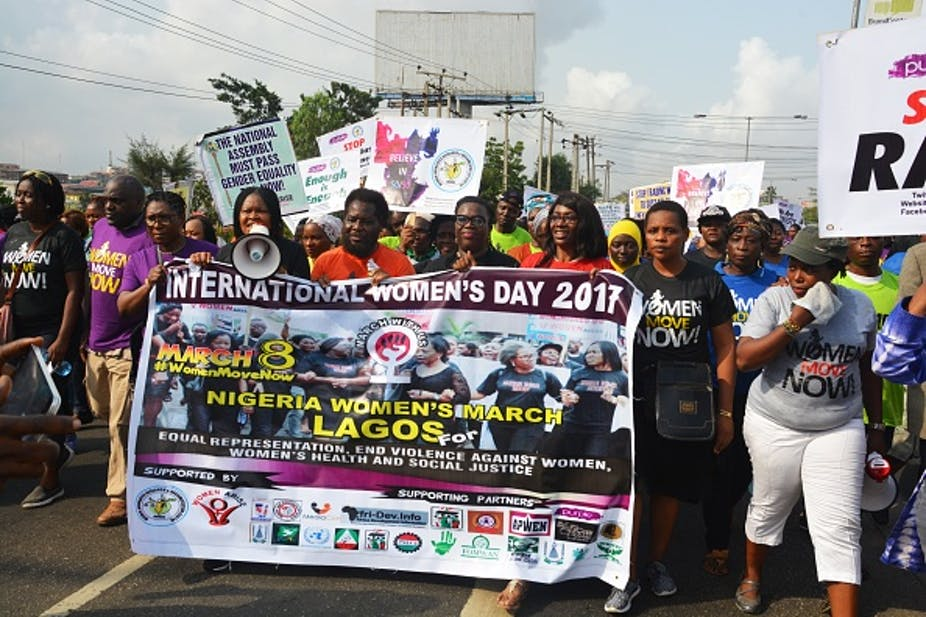 Women holding protest placards and banners.