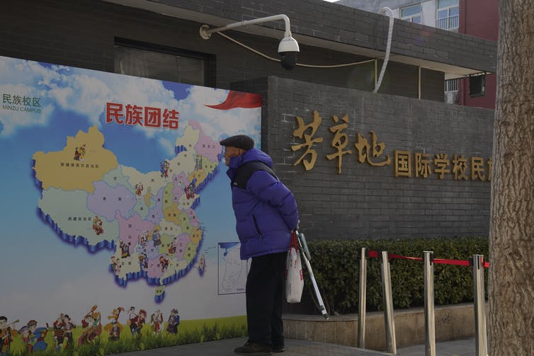 An elderly man looks at map of China showing different ethnic groups and the slogan 'Ethnic Unity.'