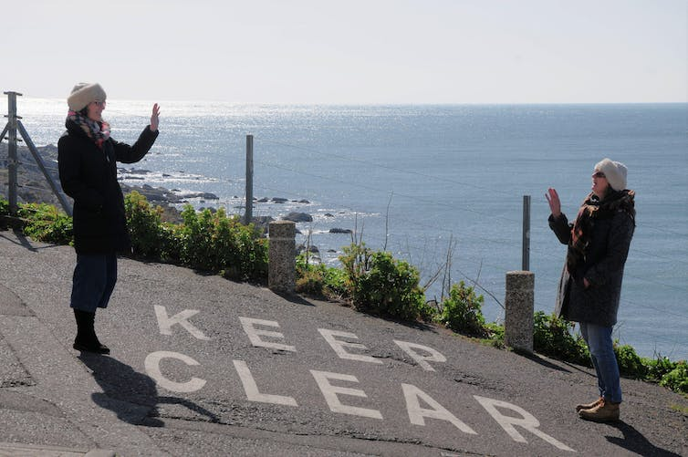 Two people wave to each other from a distance.