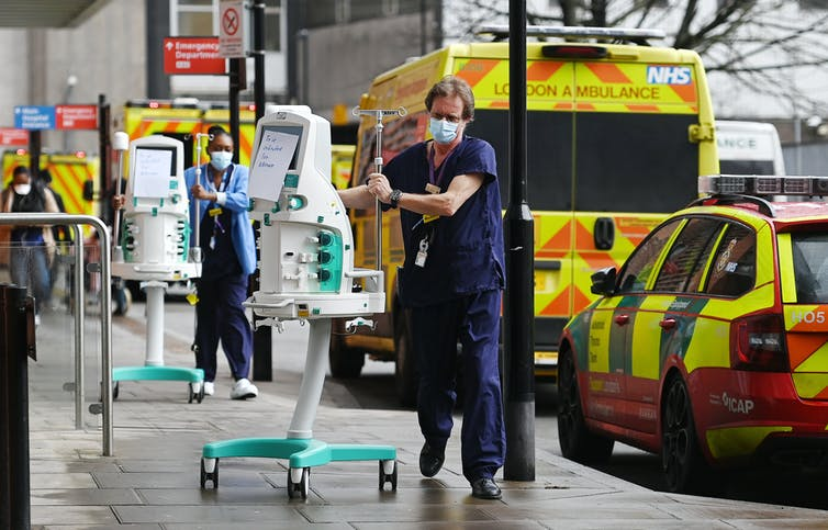 Two NHS workers wheel medical equipments into a hospital.