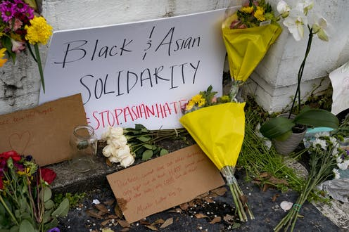 Flowers and a sign reading 'Black & Asian Solidarity STOP ASIAN HATE' lean on a white wall