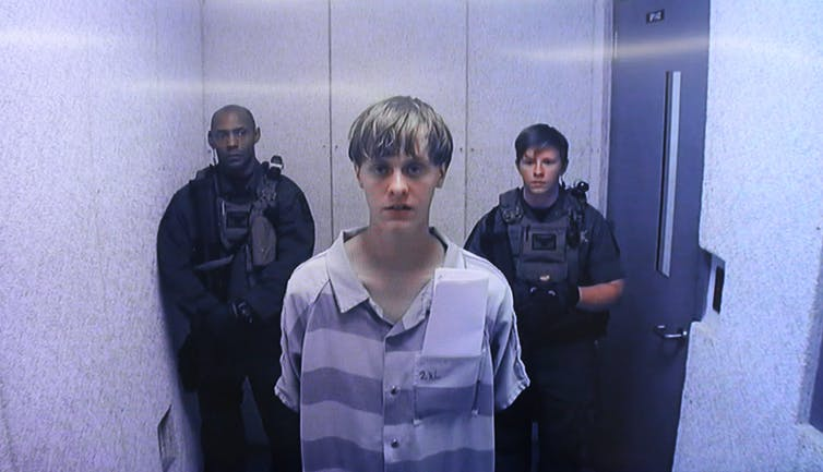 Video still of young blond man in prison jumpsuit surrounded by armed guards