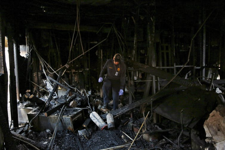 Fire inspector walks through ruins of a charred building, looking at the ground