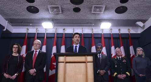 Justin Trudeau stands behind podium with ministers