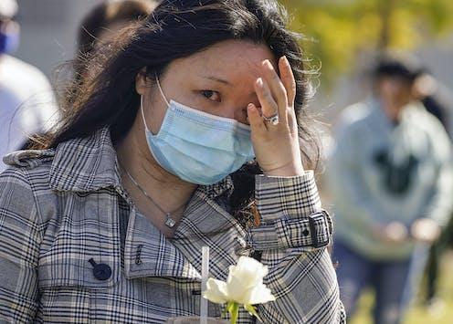 A woman wipes away tears