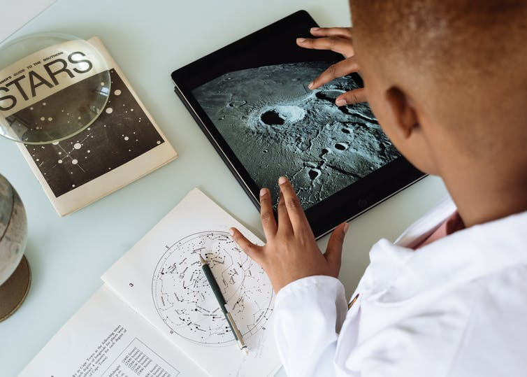 A boy with a tablet studying stars and space.