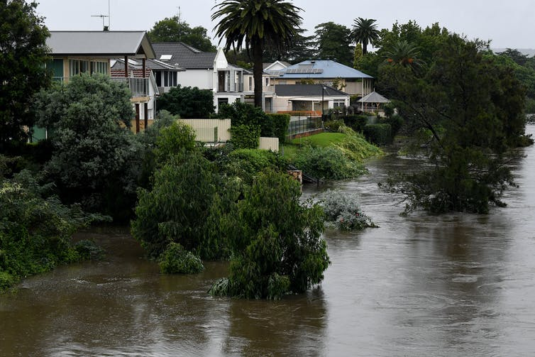 Properties are seen as the Nepean River overflows in Penrith. Rivers are bursting their banks, dams are overflowing and many NSW residents are on standby to leave their homes as heavy rain continues to pelt the state.