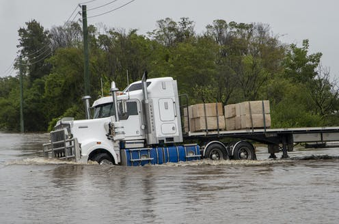 A truck drives into floodwater.