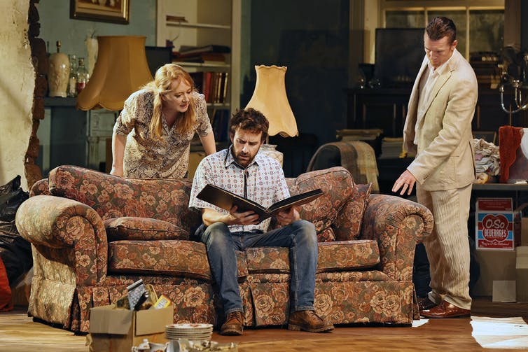 Production image. Three adults look through a photo album.