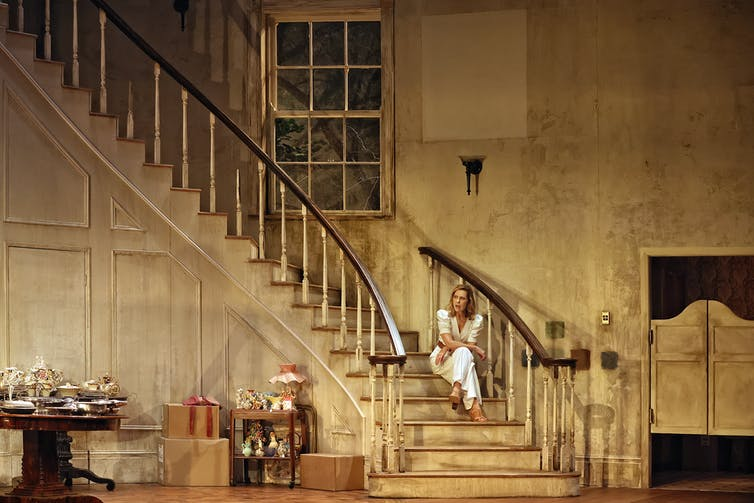 A woman sits on a sweeping staircase.