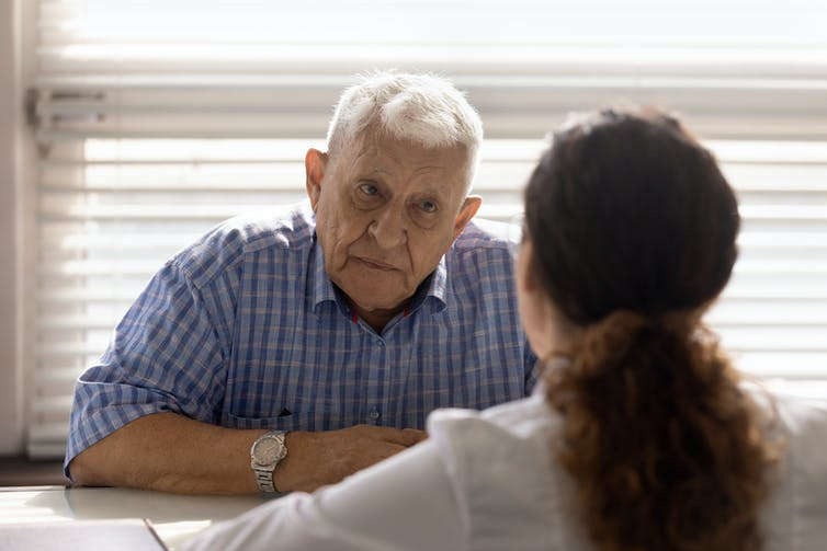 A senior man talks with a doctor.
