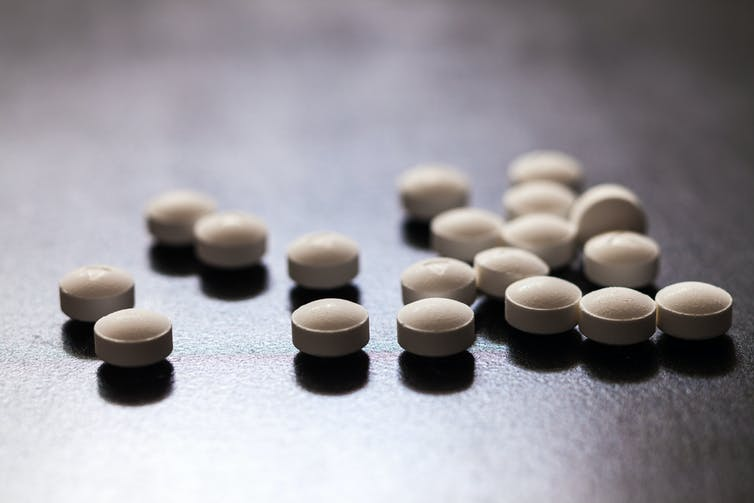 A collection of white round pills.