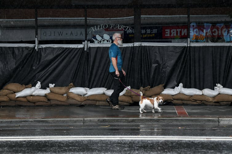 A man walks past a sand-bagged business